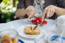 Жіночих рук різко шматок тісто на плиті з ножем та виделкою на садовий стіл — стокове фото
