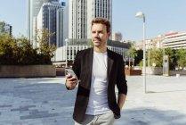 Hombre elegante con smartphone mientras está parado en la calle de la ciudad moderna - foto de stock