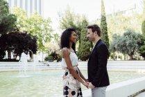 Милий елегантний пара, тримаючись за руки біля фонтану — стокове фото