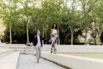 Charming black woman smiling and walking on fountain border with boyfriend in park — Stock Photo