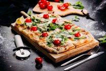 Pizza taglio rettangolare con pomodorini, bianco e formaggio sulla tavola di legno sulla tavola scura — Foto stock
