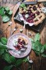 Posa piatta di torta di ciliegie al forno con crosta di reticolo servita con gelato su tavolo rustico con foglie verdi — Foto stock