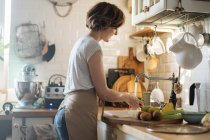 Woman washing fruits and vegetables in sink under stream of fresh water in kitchen — Stock Photo
