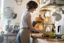Женщина, мытья фруктов и овощей в раковине под поток пресной воды в кухне — стоковое фото