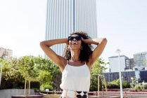 Elegant African-American woman laughing while walking on street of modern city on sunny day — Stock Photo