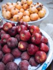 Schalen mit frischen Äpfeln und Granatäpfeln am Bauernmarkt — Stockfoto