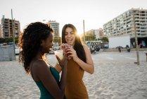 Молодые женщины, наслаждаясь напитками на пляже города в солнечном свете — стоковое фото