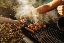 Human hands preparing bacon and sausages on skewers grilling on burning charcoal in portable griddle outdoors — Stock Photo