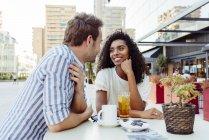 Romantisches gemischtrassige paar zusammensitzen im Café im freien — Stockfoto