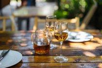 Gros plan des verres de vin blanc et pichet sur la table en bois — Photo de stock