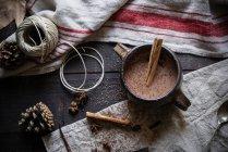 Горячий шоколад с корицей в кружке на деревенском фоне — стоковое фото