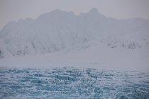 Ghiaccio galleggiante in acqua con silhouette di montagne sullo sfondo, Svalbard, Norvegia — Foto stock