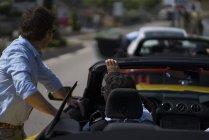 Mann sitzt in modernem Neuwagen und spricht mit Mann, der in der Nähe steht und sich auf Auto stützt — Stockfoto