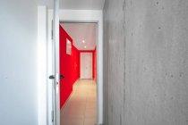 Interior do corredor de escritório vermelho através da porta aberta no edifício moderno — Fotografia de Stock