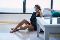 Молода жінка вдумливі, сидячи на підлозі біля дивана — стокове фото