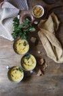 Sopa de crema de maíz con coco y pesto en cuencos sobre mesa de madera con ingredientes - foto de stock