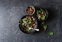 Insalata con verdure, formaggio e mandorle in ciotole su superficie grigia — Foto stock