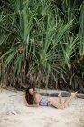 Jeune femme en maillot de bain couché sur le sable sur la plage tropicale — Photo de stock