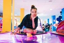 Junge Frau liegt auf Airhockeytisch und blickt in Kamera — Stockfoto