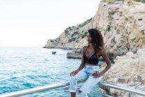 Elegante mujer afroamericana en jeans y la parte superior sentado en la valla contra pintorescos acantilados y paisajes marinos - foto de stock