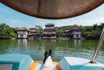 Jambes de l'homme couché sur le bateau tout en flottant sur le lac tropical dans le parc exotique de la montagne Qingxiu, Nanning, Chine — Photo de stock