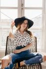 Elegante giovane donna in cappello seduta sulla sedia e guardando la fotocamera — Foto stock