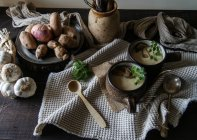 Bowls of tasty Jerusalem artichoke soup with ingredients on rustic wooden table — Stock Photo