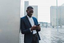 Молодой человек в элегантном костюме, стоящий, опираясь на стену здания и используя мобильный телефон — стоковое фото