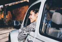 Young woman sitting inside retro car in countryside and looking away — Stock Photo