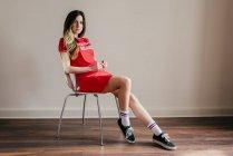 Bella donna in abito rosso seduta sulla sedia — Foto stock