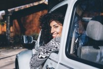 Young woman sitting inside retro car in countryside and looking at camera — Stock Photo