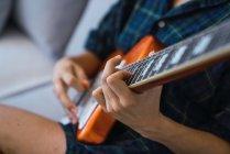 Крупный план женских рук, играющих на гитаре — стоковое фото