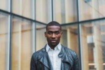 Nero uomo d'affari in giacca di pelle in piedi contro edificio — Foto stock