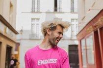 Стильний мужчина зі світлим волоссям і рожева Маєчка позують вулиці — стокове фото