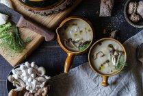 Servis dans des bols savoureux champignons crème sur une table en bois rustique avec des ingrédients — Photo de stock