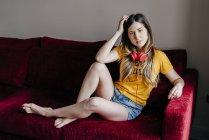 Donna con le cuffie seduta sul divano e guardando la fotocamera — Foto stock