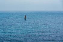 Парусник на поверхности океанской воды под голубым небом — стоковое фото