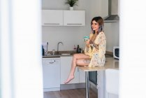 Allegro giovane donna tatuata seduta sul tavolo in cucina con tazza di bevanda calda — Foto stock