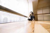 Donna che prende un caffè mentre è seduta sul pavimento in classe di danza — Foto stock