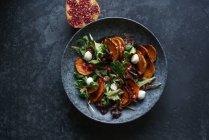 Салат з овочами і сиру в миску на сірому поверхні з гранатом половина — стокове фото
