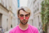 Портрет стильний мужчина в рожевий серцеподібне сонцезахисні окуляри стоячи на вулиці — стокове фото