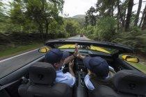 Чоловіки, водіння в сучасних швидкий автомобіль по дорозі в сільській місцевості — стокове фото
