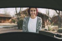 Jeune femme en chapeau de laine debout derrière la voiture dans la campagne — Photo de stock