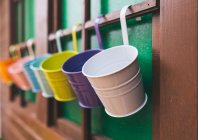 Colorful plant pots hanging on wooden wall — Stock Photo