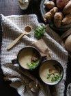 Tazones de fuente de sabrosa sopa de alcachofa de Jerusalén con los ingredientes en la mesa de madera rústica - foto de stock