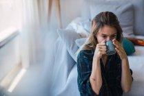 Jovem mulher desfrutando de bebida quente enquanto sentado perto do sofá no quarto aconchegante — Fotografia de Stock