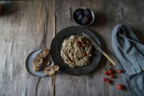 Artichoke dip served with cherry tomatoes in black plate on rustic wooden table — Stock Photo
