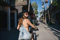 Веселий жінка, озираючись назад, коли він їхав на скутера на вулиці в Таїланді — стокове фото