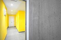 Porta aperta al moderno corridoio giallo — Foto stock