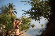 Молодая женщина отдыхает с закрытыми глазами на берегу моря в Таиланде — стоковое фото